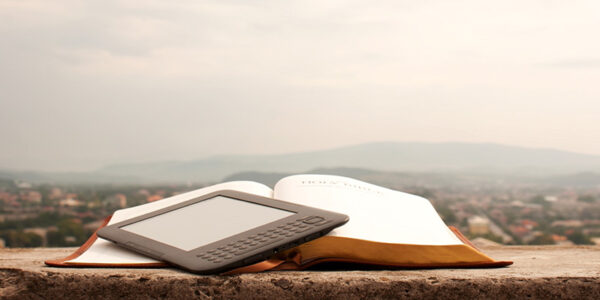 Electronic book reader laying on the book outdoors
